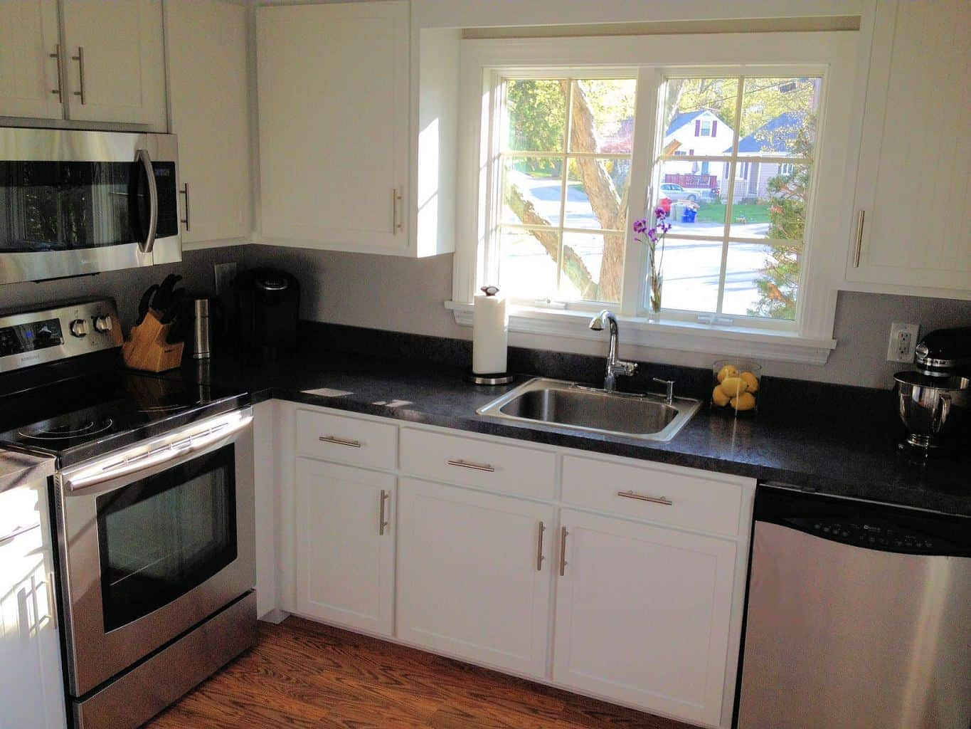 A kitchen with a large window above a kitchen sink, white cabinets and dark countertops