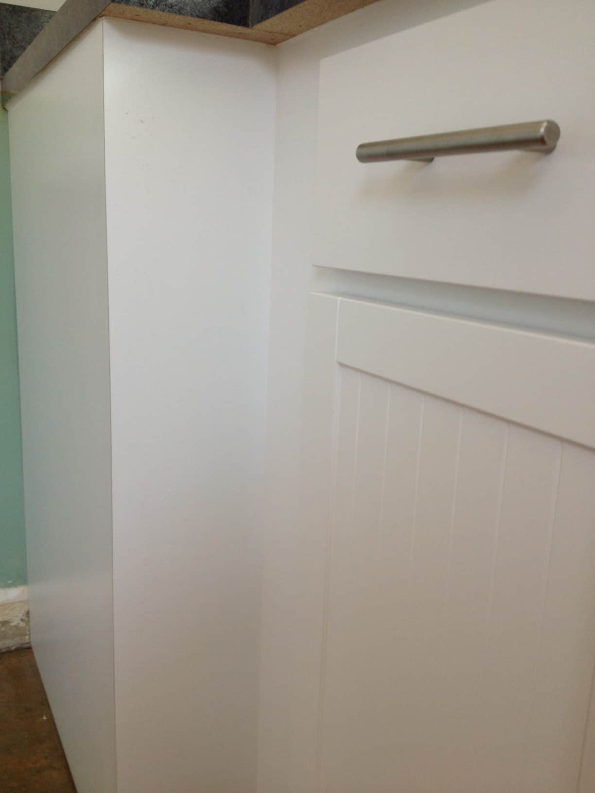 A close up of a white drawer of a kitchen cabinet, with a silver handle
