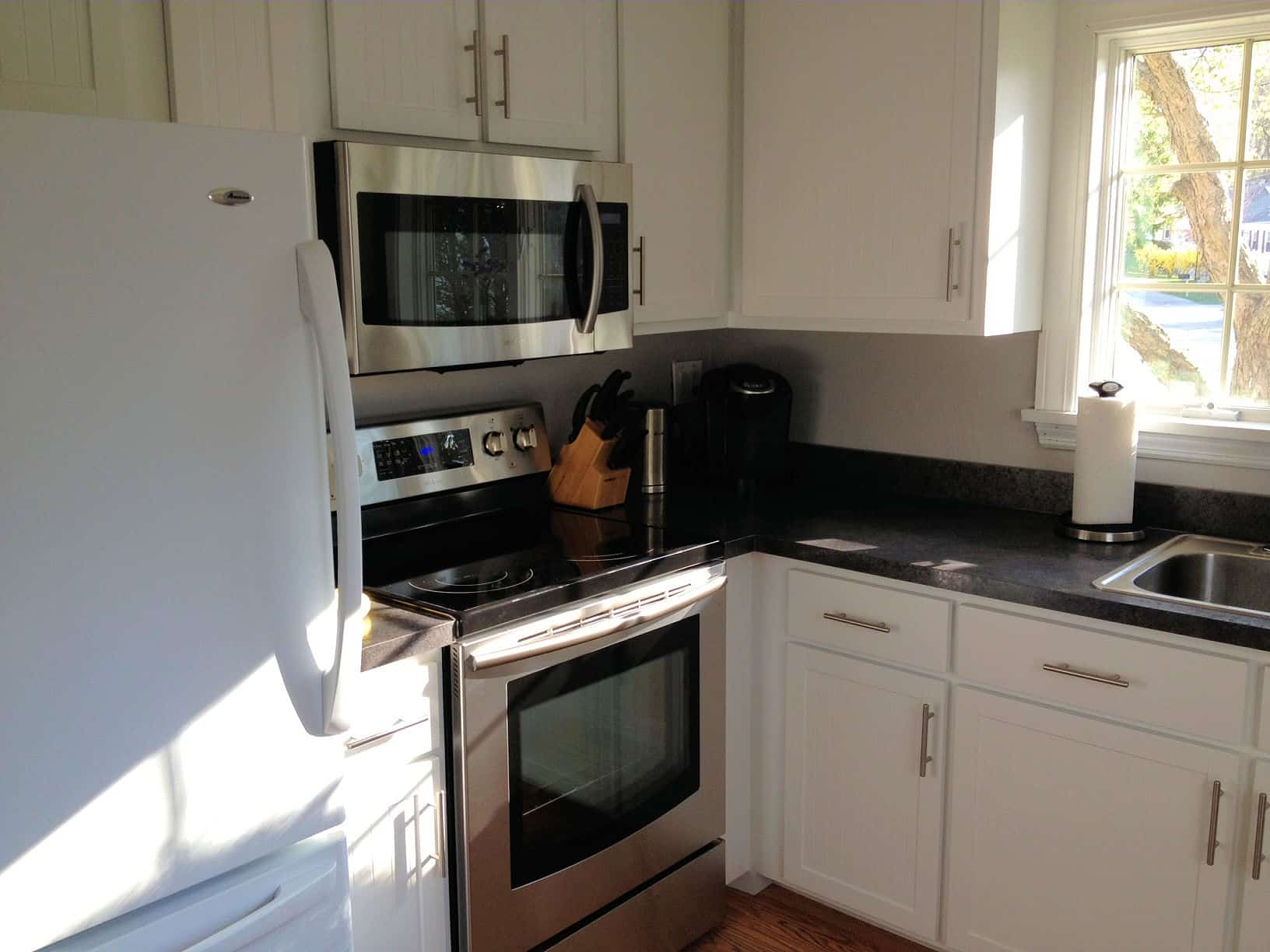 The corner of a kitchen, with white cabinets, stainless steel stove and microwave and a white fridge