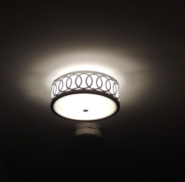 New lighting fixture at night, with white glow on ceiling and circular pattern on trim of fixture