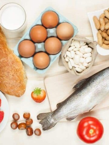 A display of food items such as a loaf of bread, eggs, white beans, strawberries, tomatoes, nuts, and a whole fish