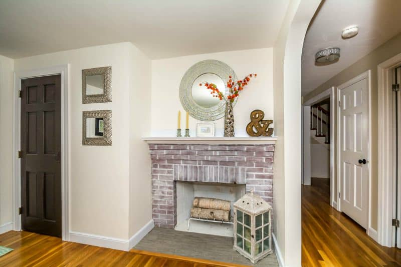Dove gray walls and trim next to a whitewashed red brick fireplace
