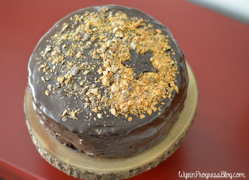 A close up of the top of a chocolate-frosted cake with crunchy bits on top