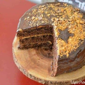 A chocolate cake, with a large wedge cut out, resting on a rustic, wood cutting