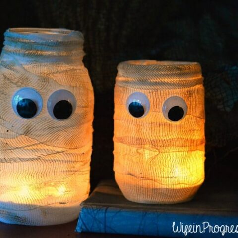 2 mason jars wrapped with gauze, and decorated with two plastic eyeballs for a mummy-inspired lamp
