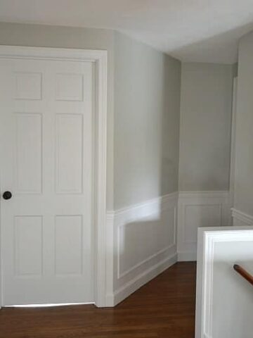 upstairs hallway with doors and wainscoting painted benjamin moore decorator's white