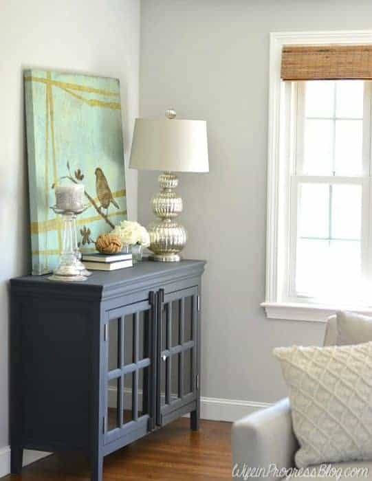 The simple black paint on this cabinet makes it a sleek and modern piece. I love the lamp and accessories on top!