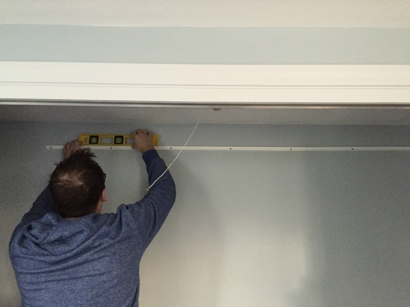A person holding a level at the top of the inside of the closet