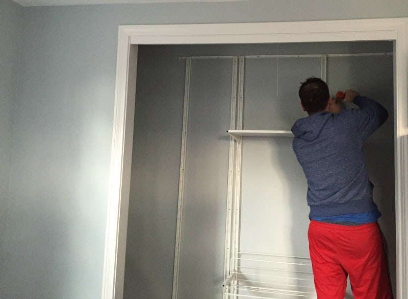 A person in a closet, installing shelves and framework for a closet system