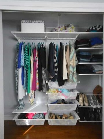 A closet with two rods of clothing, an upper shelf across the width of the closet and shelves and drawers in various sections around the rods