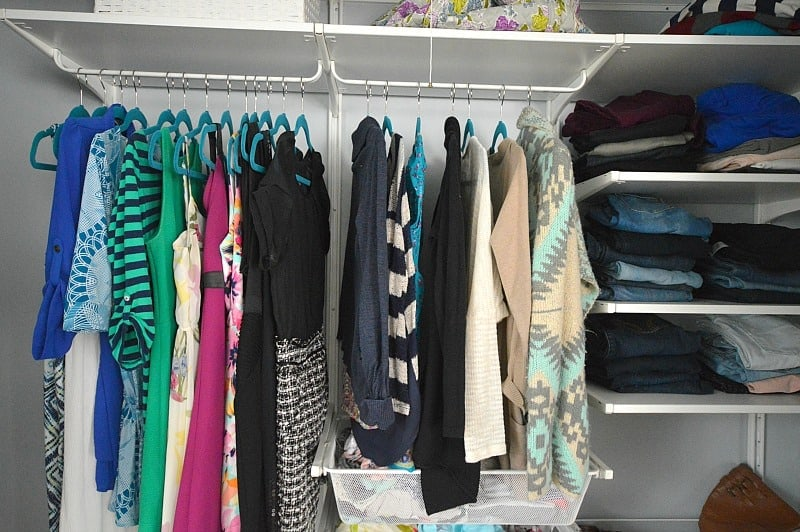Colorful dresses, sweaters, tops and jeans hung up or stacked on the shelves of a new closet organizer system
