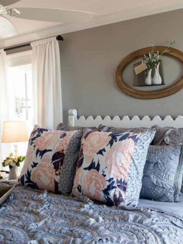 A bed with a white, wooden headboard, textured grey bedding set with large, floral accent pillows and a wooden, oval frame on the wall above
