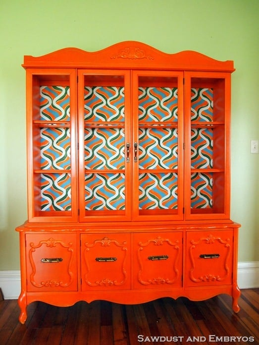 This updated china cabinet is a bold statement piece with bright orange paint and the colorful background pattern