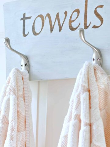 2 towels hung on metal hooks on painted wooden plank, with the word 'towels' in decal sticker