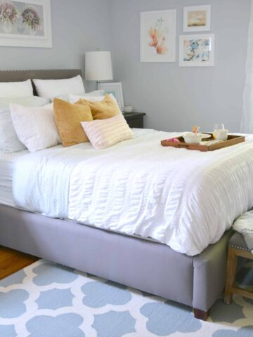 A bedroom with a blue and white area rug, a bed with white bedding and gold accent pillows, a tray of breakfast items and a bench at the end of the bed