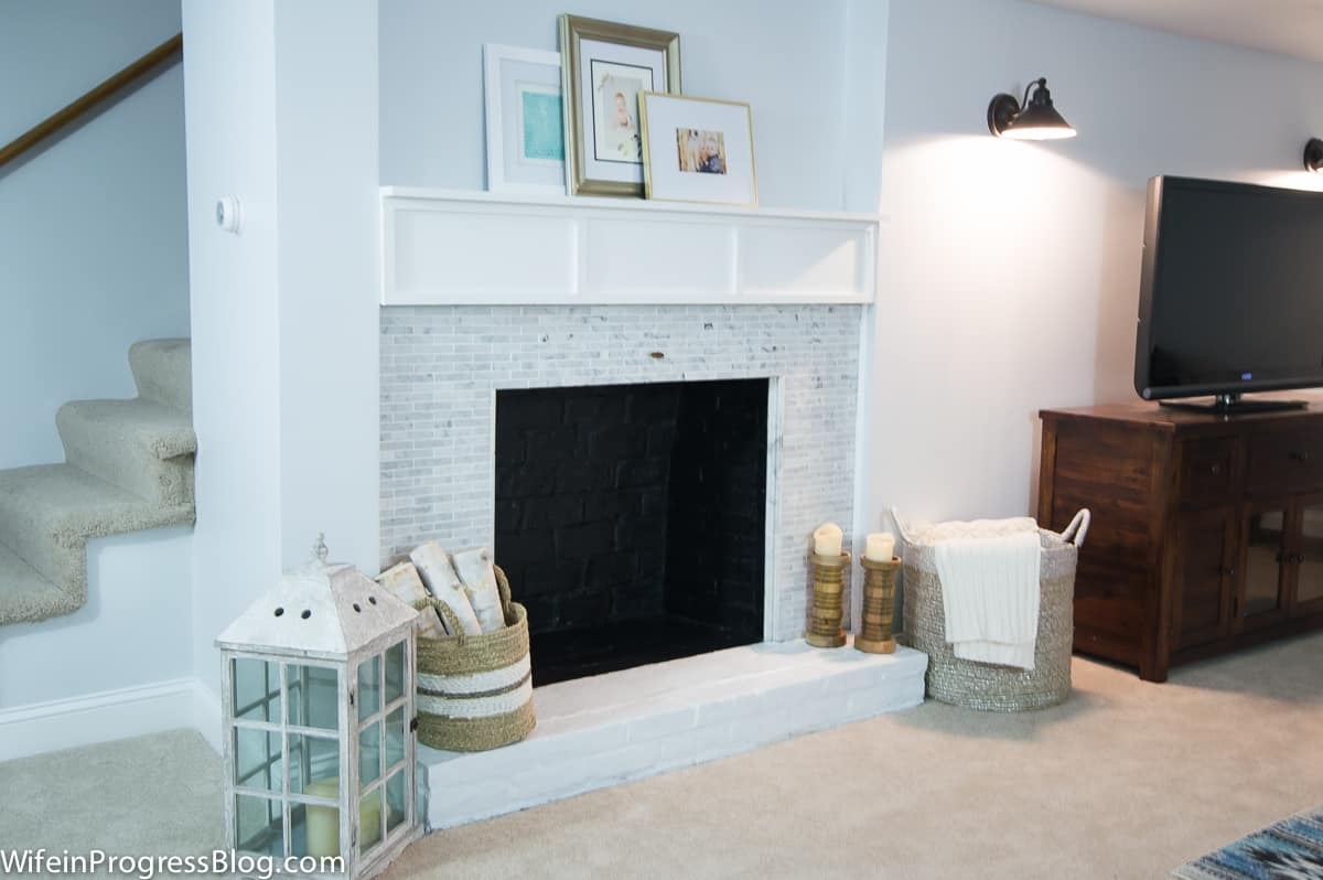 A living room with fireplace, paintings loosely arranged on the mantel, wicker baskets and a large glass lantern nearby