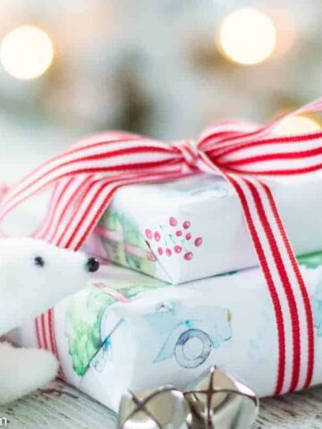 Two wrapped gifts tied with red and white ribbon, sitting on a table next to holiday decor