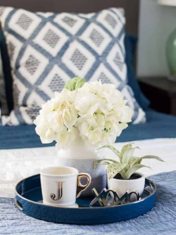 """A round, blue tray on a bed, holding a gold/white mug with the initial """"J"""", a blue vase with white flowers, and a small potted plant"""