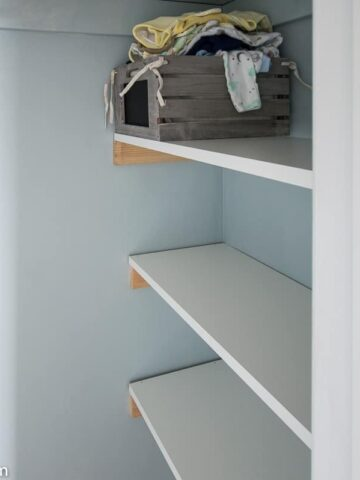 A trio of melamine shelves in the side of the closet, with unpainted cleats/braces supporting each shelf. A basket of baby bibs rests on top of one.