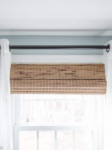 A top view of a window with a black curtain rod, white sheer grommet curtains and rolled up bamboo shades