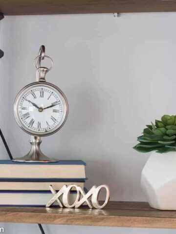 An antique silver clock, resting on a stack of books with the pages facing outward, near a potted plant on a wooden shelf