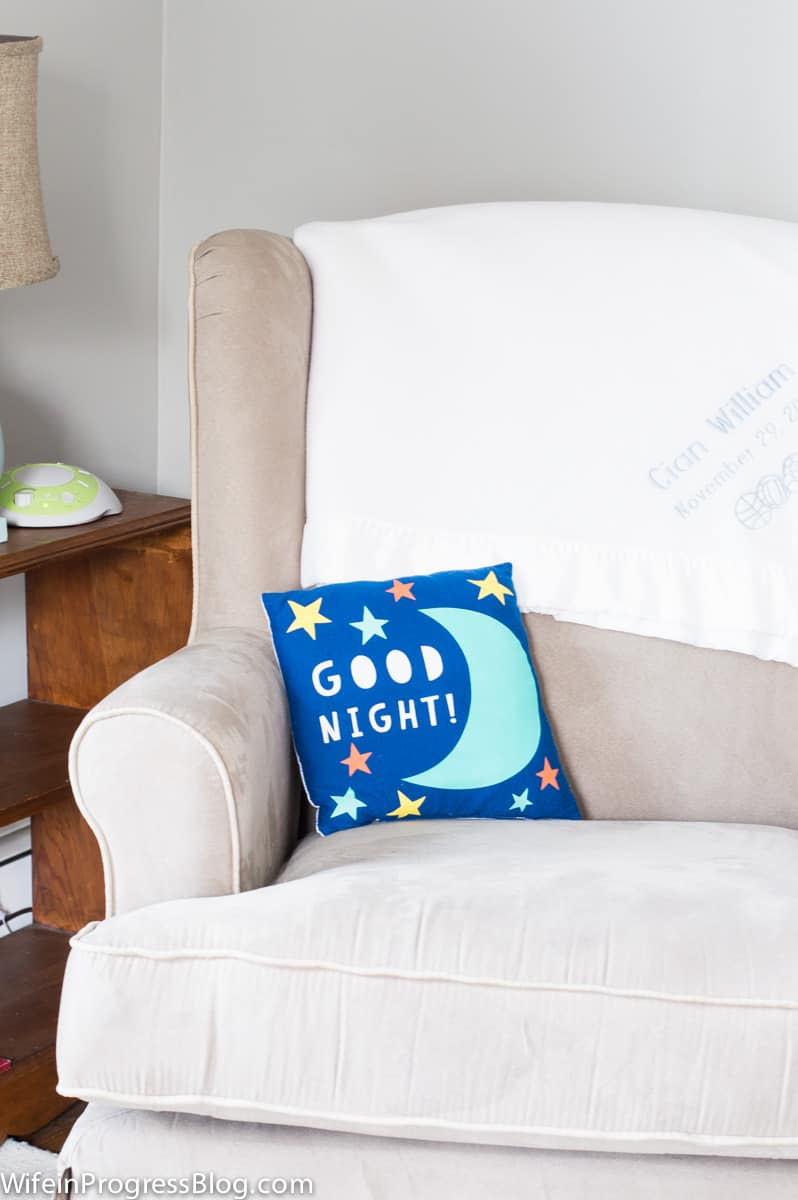 """A beige armchair with a personalized, white blanket and a small blue pillow with the words \""""Good Night!\"""""""