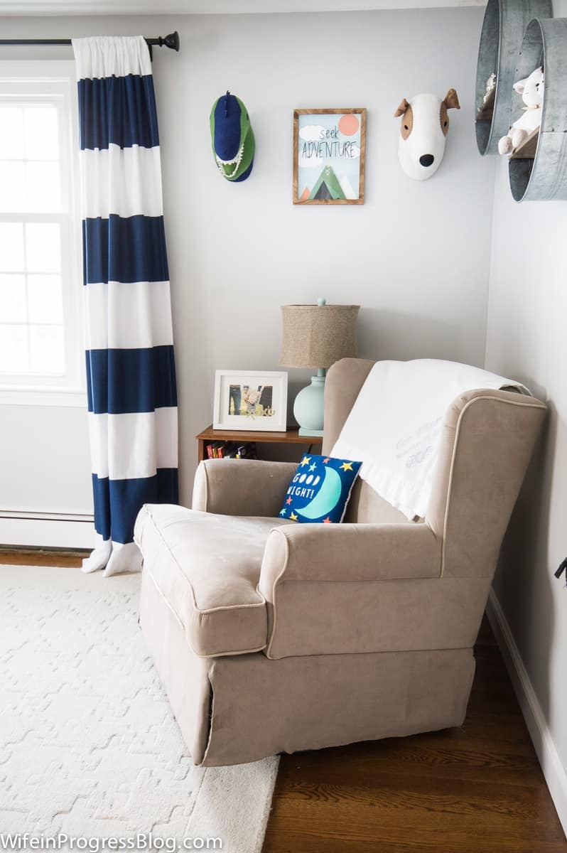 A nursery with beige, armchair rocker, blue and white curtains, and galvanized buckets mounted on the wall to hold stuffed animals