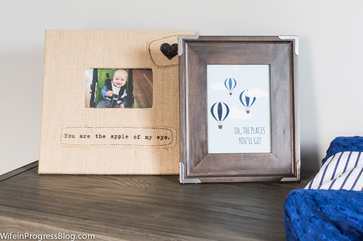 """A beige photo frame of a baby with the words \""""You are the apple of my eye\"""" and a dark wooden frame with balloons and the words \""""Oh the places you\'ll go!\"""""""
