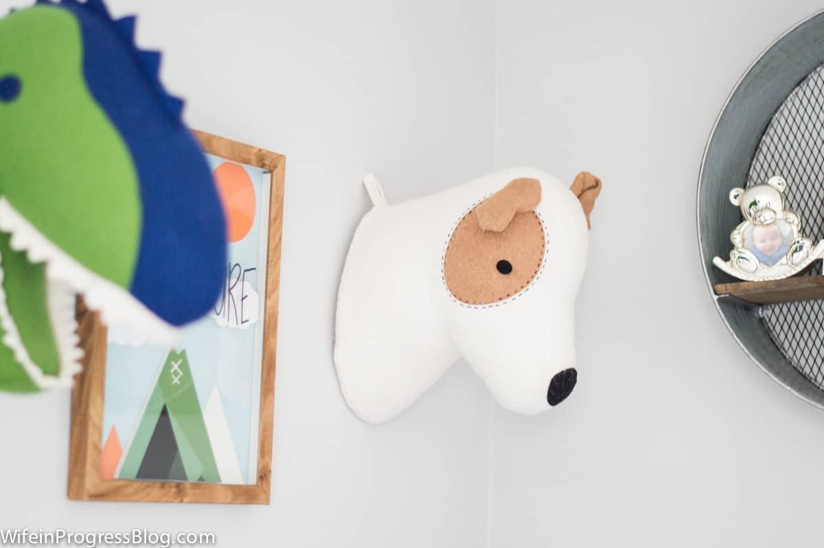 A stuffed animal mounted on the wall, near wall art