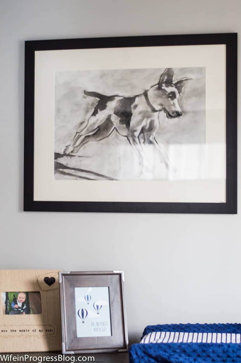 A large drawing of a dog on white matting and a dark frame, hung over a side table in a baby\'s room