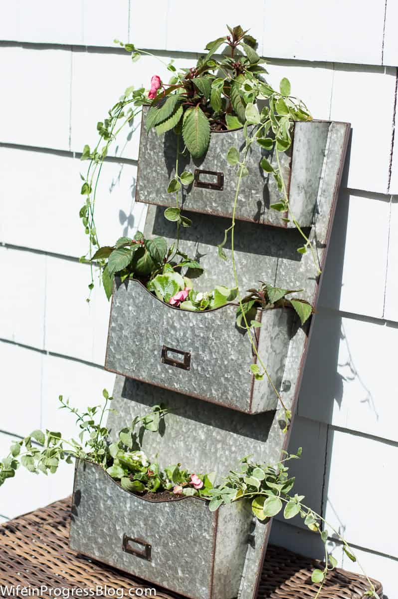 Farmhouse planter using a 3-tiered metal mail holder, resting on an outdoor wicker side table