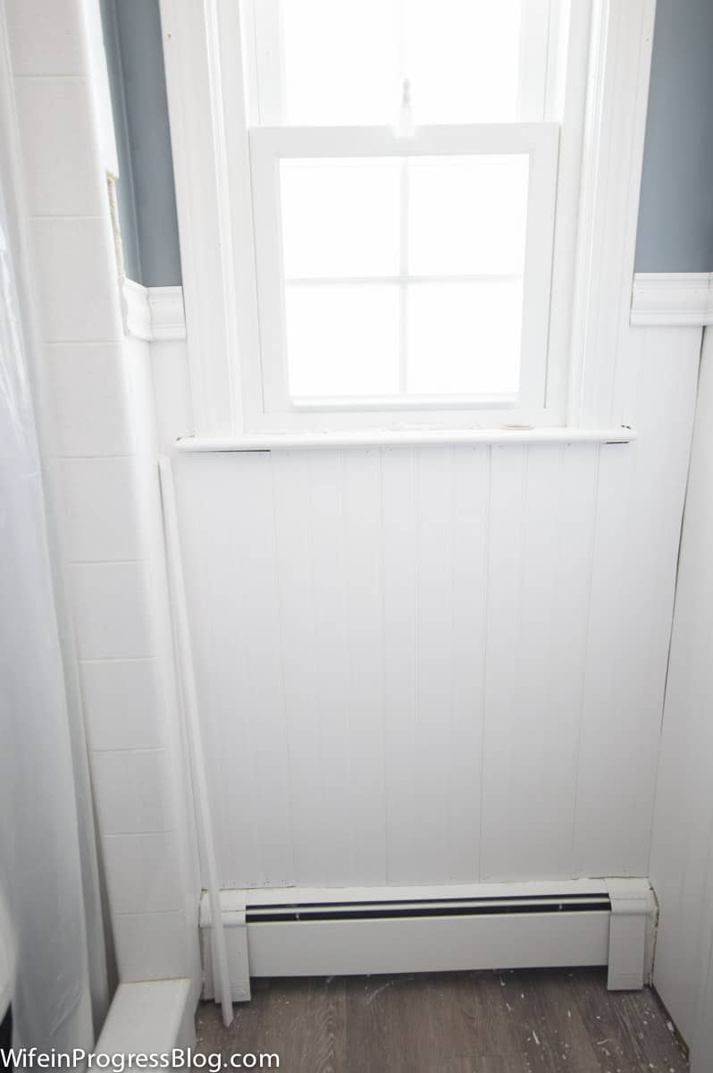 Bright window above vinyl wainscoting, with shower on left