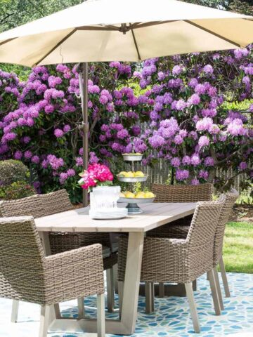 A beige umbrella on a light brown patio table with six wicker chairs, on blue mosaic tiles, and purple flowering shrubs in the background