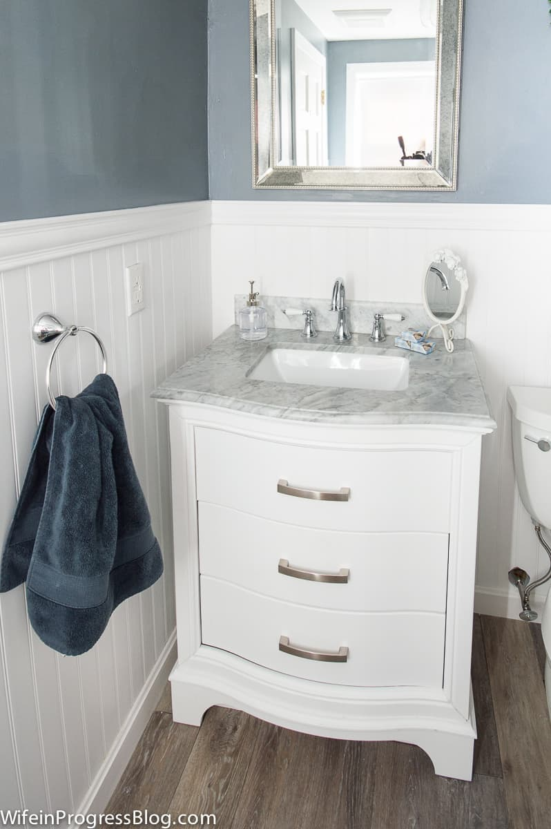 I love the sleek white marble on our new vanity and how well it pairs with the new vinyl wall covering