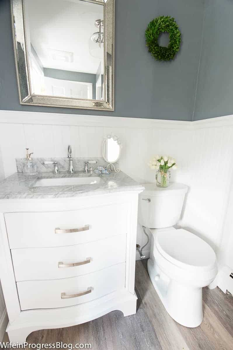 A bathroom with a white vanity sink, white toilet, white wainscoting, grey walls and a large, rectangular mirror with silver trim