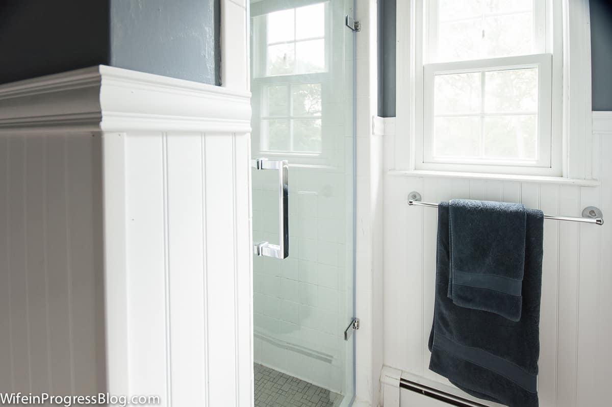 My favorite part of this budget-friendly master bathroom makeover is this single pane glass shower door