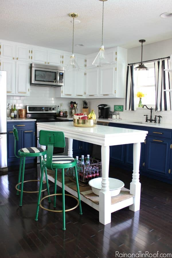 A kitchen with white upper cabinets, dark blue lower cabinets and a tall, white table as an island, with dark green metal stools