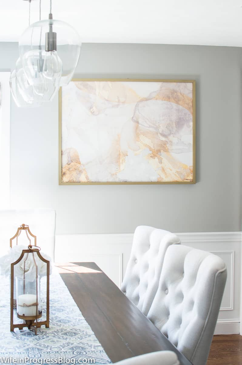 Dining room walls painted gray with large art hanging. Wainscoting is painted Benjamin Moore decorators white