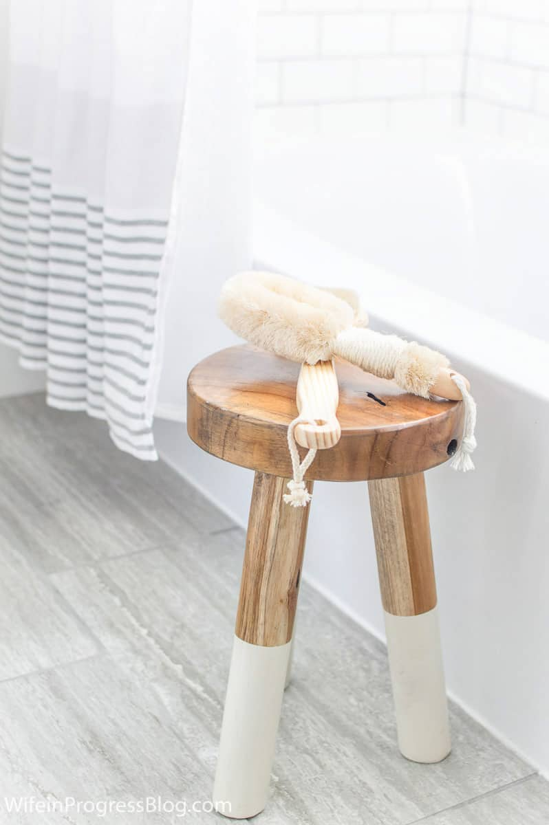 Bath accessories resting on wooden bath stool with painted legs