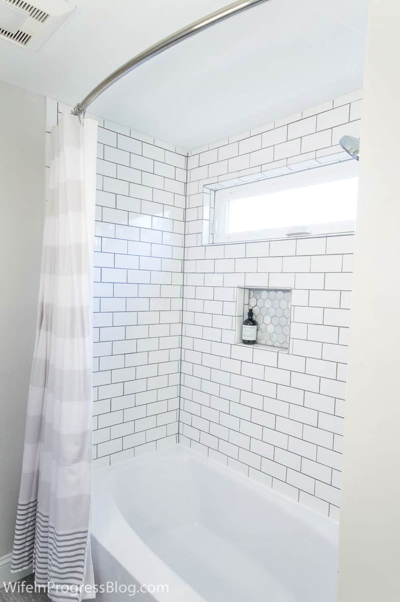 Delorean gray grout on the subway tiles around a freshly-lined bathtub
