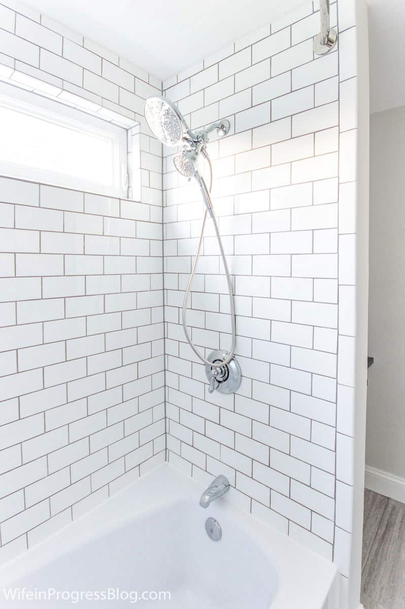 Chrome shower head, knob and faucet in bathtub area, surrounded by white subway tiles and gray grout