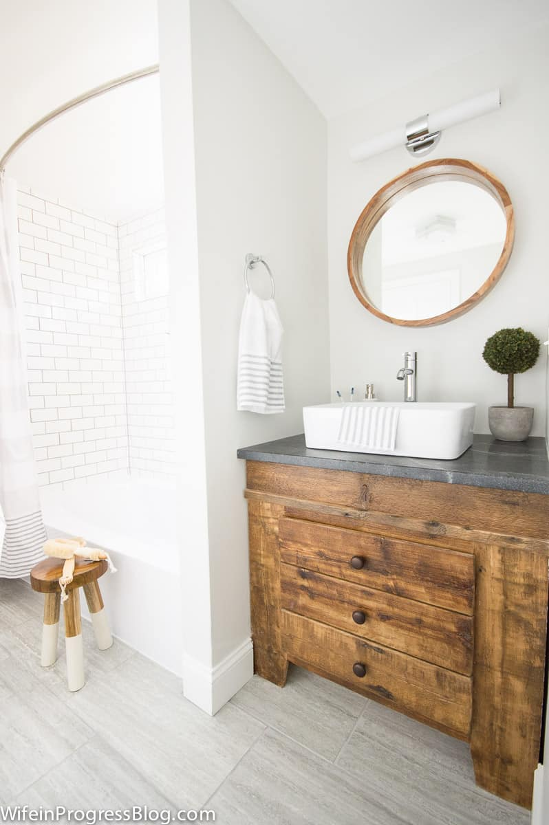 Modern farmhouse bathroom remodel with reclaimed wood vanity. This bathroom used to be completely pink but look at it now!