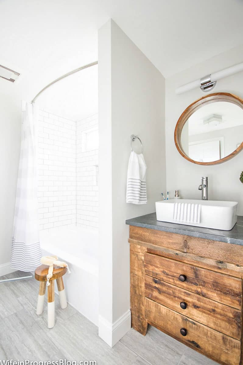 Vanity with farmhouse sink and wood  door that looks like three drawers but swings open