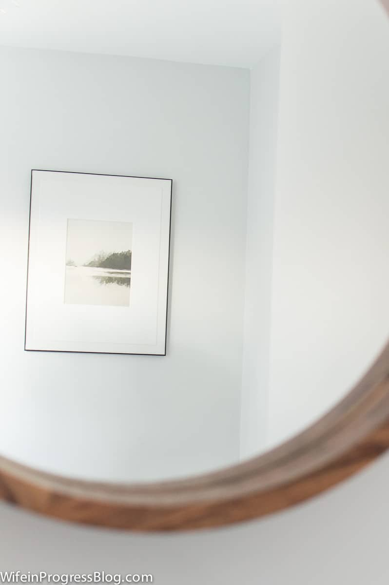 Reflection of framed landscape print through the round wood mirror are well-suited to a modern farmhouse bathroom