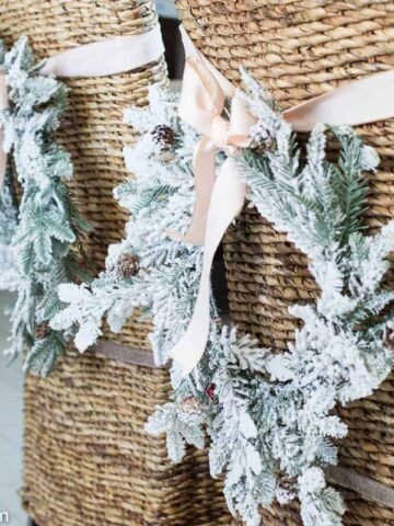 Christmas wreaths tied to the back of tall, wicker chairs with light pink ribbon