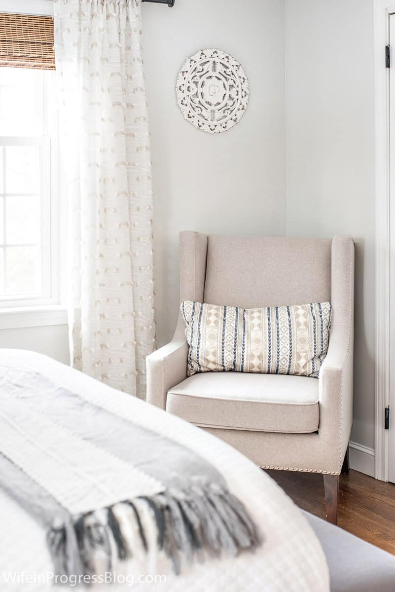 A neutral chair arrange in the corner of this small master bedroom adds functionality to the space