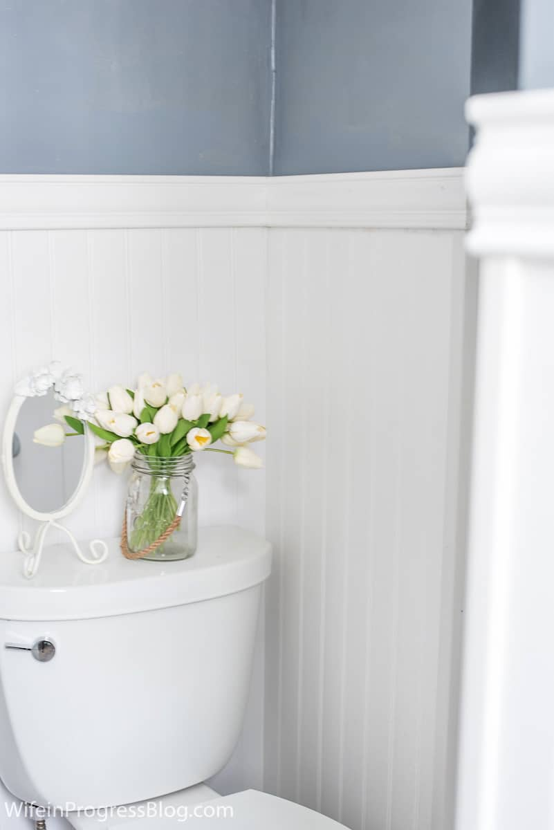 The finishing touches - antique mirror and vase of white flowers sit on toilet, framed by new beadboard wainscoting