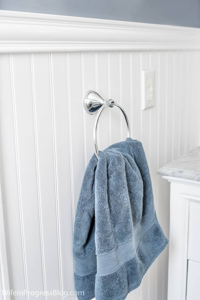 Another angle of room, where chrome towel hanger holds blue towel, against new wainscoting