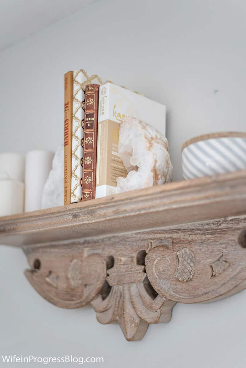 A floating shelf on the wall of this rustic and charming master bedroom makeover