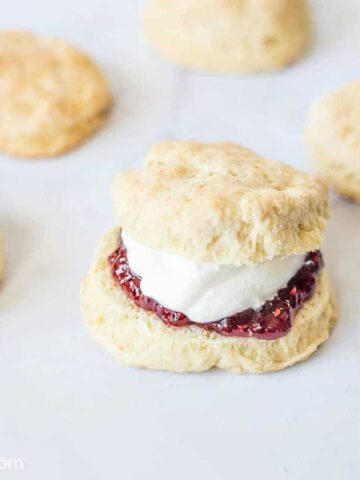 Scones on a baking pan, with one sliced open and filled with jam and cream